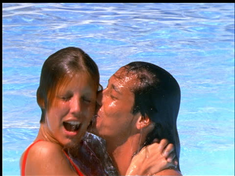 slow motion close up couple emerges from swimming pool hugging - 室外プール点の映像素材/bロール