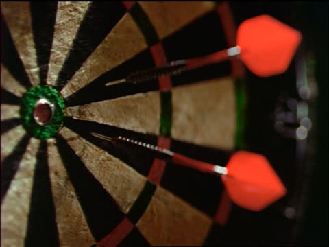 stockvideo's en b-roll-footage met slow motion close up dart hitting bullseye on dartboard with two other darts on it - kleine groep dingen