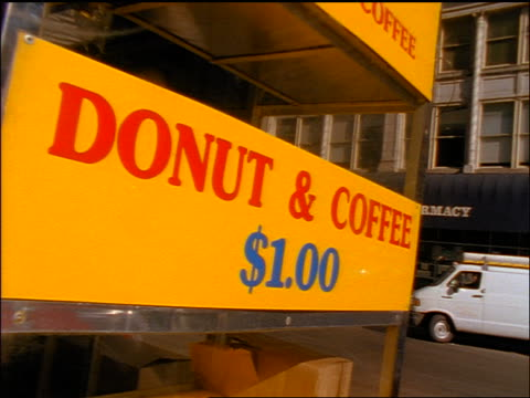 "slow motion close up pan ""donuts & coffee $1.00"" sign on street vendor cart / nyc - cart stock videos & royalty-free footage"