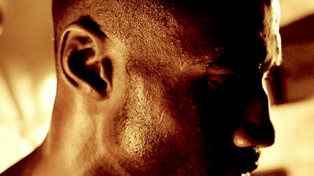 vídeos de stock, filmes e b-roll de slow motion close up face of black man sweating and turning - suor