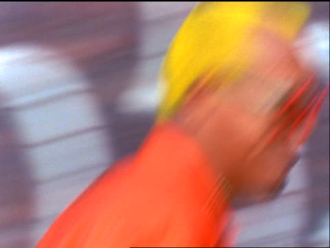 slow motion close up face of man with yellow hair in wacky star-shaped sunglasses skating past camera / NYC