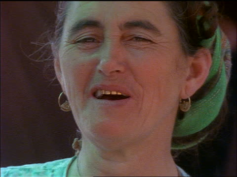 slow motion close up face of middle aged Russian woman smiling + talking