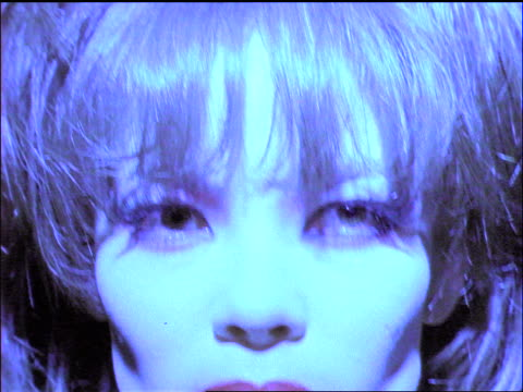 blue slow motion close up face of woman with big hair poses for camera - big hair stock videos and b-roll footage
