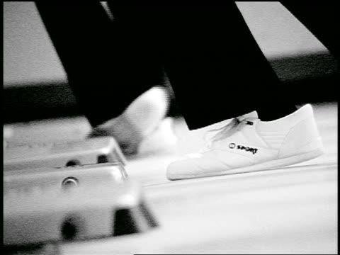 vídeos de stock, filmes e b-roll de b/w slow motion close up feet with bowling shoes sliding on floor as bowling balls are thrown in bowling alley - cancha de jogo de boliche