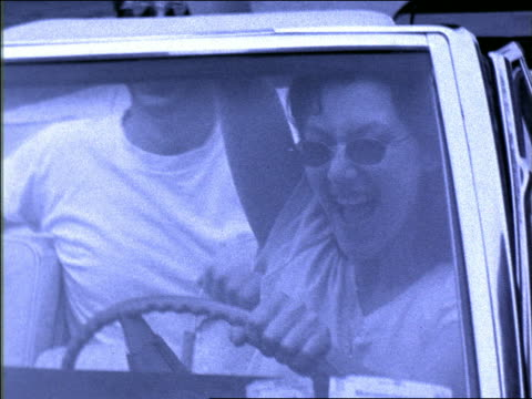 b/w blue slow motion close up gen x couple driving in convertible laughing + shouting - x世代点の映像素材/bロール