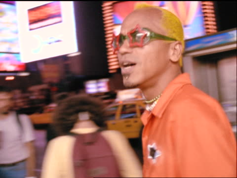 slow motion close up pan gen x man in sunglasses skating past camera in times square at night - x世代点の映像素材/bロール