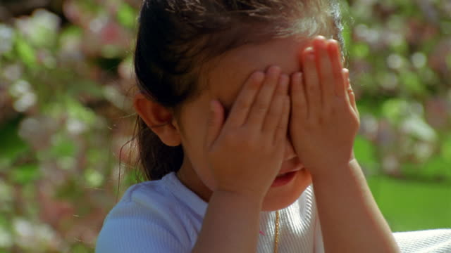 slow motion close up girl uncovers hands from eyes outdoors - hide and seek stock videos and b-roll footage