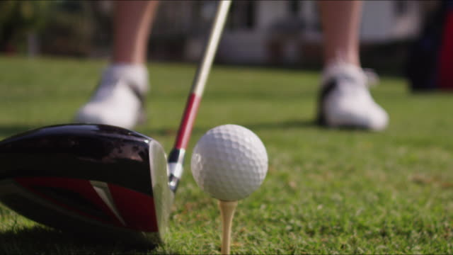 Slow motion close up golf ball on tee, large driver fills the lens, golfer prepares to swing, swings and misses the ball sfx.