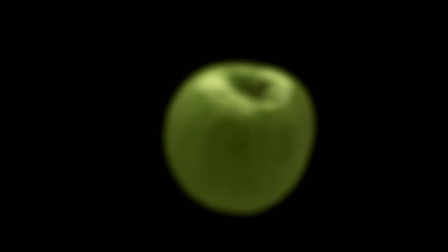 slow motion close up green apple coming into focus as it moves towards camera / defocus as it falls away - approaching stock videos & royalty-free footage