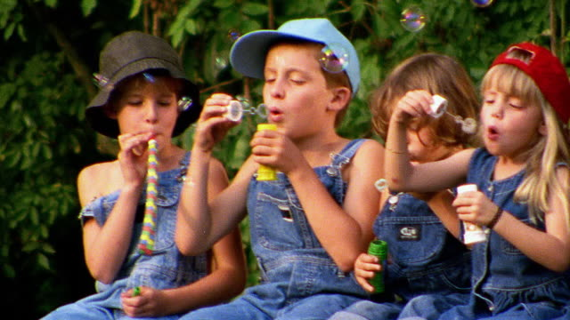 slow motion close up PAN group of children in overalls blowing bubbles sitting on bridge