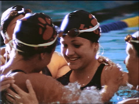 slow motion close up group of swim team women in bathing caps + goggles hugging after race in pool - 室外プール点の映像素材/bロール