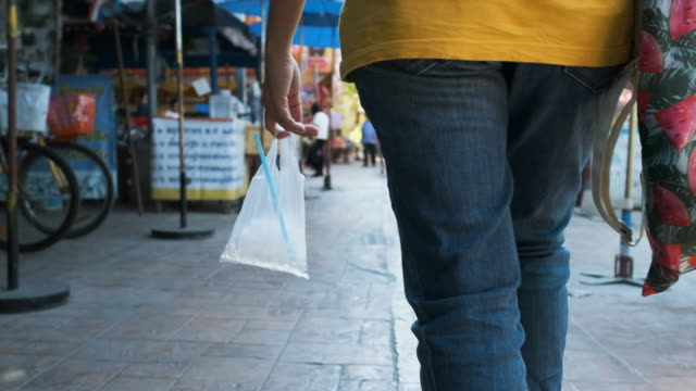 slow motion close up hand holding ice water in plastic bag walking at street marketplace in hot weather sunny day - agricultural fair stock videos & royalty-free footage