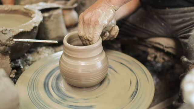 slow motion close up hand potter making earthenware vase in workshop studio - potter's wheel stock videos & royalty-free footage