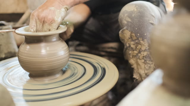 slow motion close up hand potter making earthenware vase in workshop studio.panning shot from right blur background - craftsperson stock videos & royalty-free footage