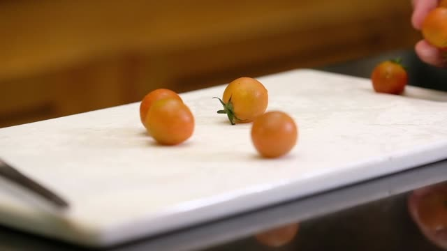 slow motion close up hand put tomato on cutting board in kitchen - rolling stock videos & royalty-free footage