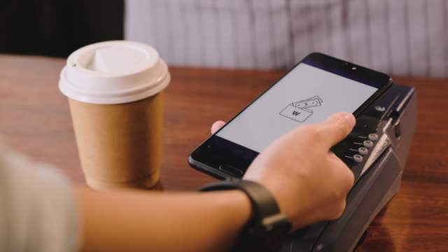 slow motion close up hand use mobile e wallet app paying contactless on credit card machine at counter bar in cafe.wireless payment nfc lifestyle - paying stock videos & royalty-free footage