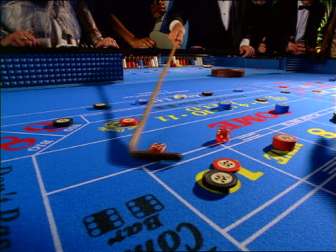 slow motion close up hands of dealer retrieving dice from craps table with cane / hand placing chips on table