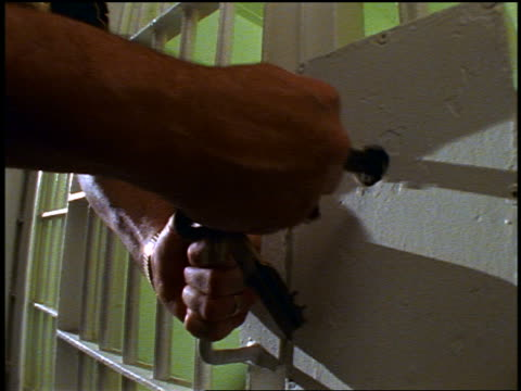 slow motion close up hands of prison guard closing + locking prison cell door with keys - jail cell stock videos & royalty-free footage