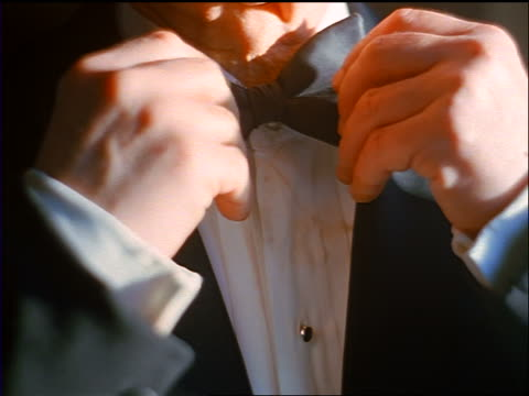 slow motion close up hands of senior man wearing tuxedo adjusting black bow tie - formal stock videos and b-roll footage