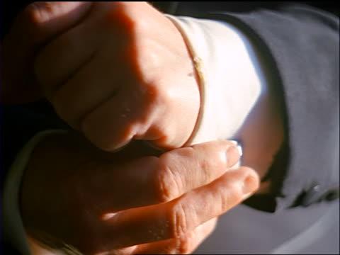 slow motion close up hands of senior man wearing tuxedo adjusting cuff link
