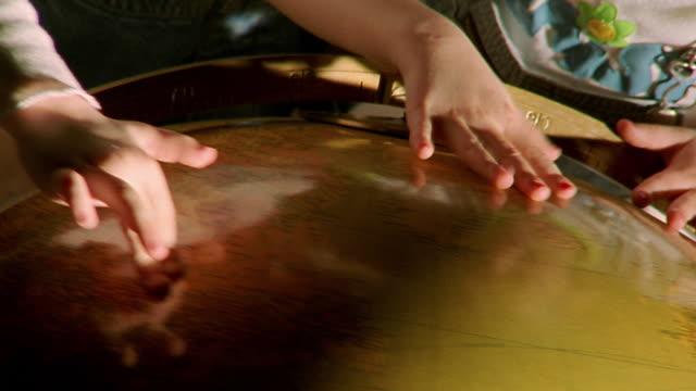 vídeos y material grabado en eventos de stock de slow motion close up hands of two young girls spinning large globe - globo terráqueo para escritorio