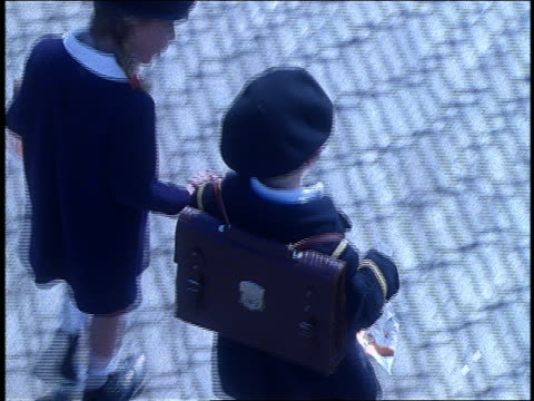 vidéos et rushes de slow motion close up high angle of 2 schoolchildren walking + holding hands - couple d'adolescents