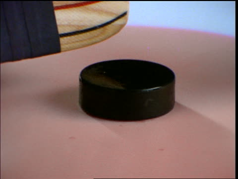 slow motion close up hockey puck dropping on ice / sticks hitting it
