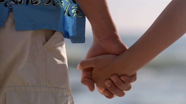 Slow motion close up holding hands/ medium shot couple walking toward ocean on beach and holding hands/ Bali, Indonesia