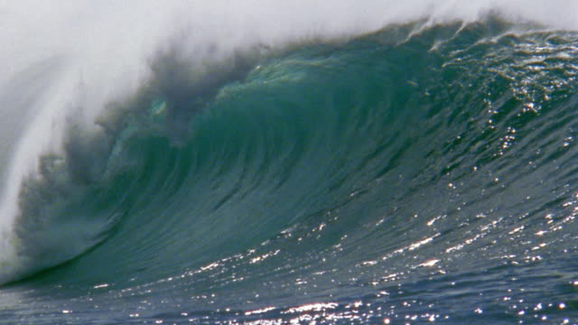 Slow motion close up large ocean wave crashing on ocean w/mist spraying / Oahu, Hawaii