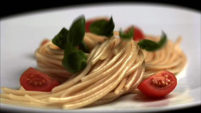 Slow motion close up leaves of basil falling on plate of pasta