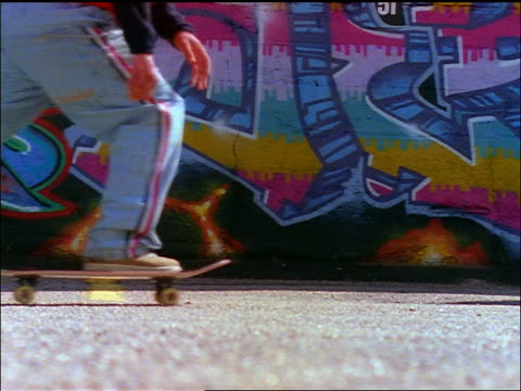 vídeos y material grabado en eventos de stock de slow motion close up legs of skateboarder going by camera / graffiti-covered wall in background - 1990