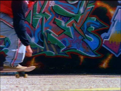 stockvideo's en b-roll-footage met slow motion close up legs of skateboarder going by camera / graffiti-covered wall in background - alleen één tienerjongen