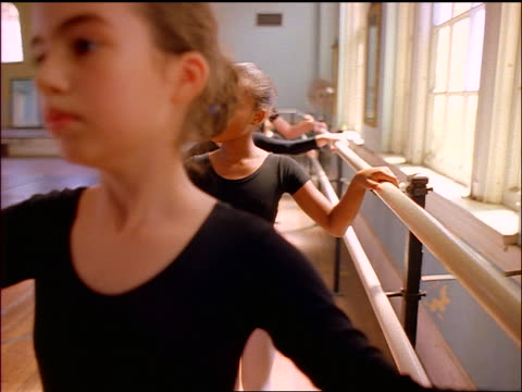 slow motion close up pan line of girls practicing exercises at barre in ballet class in dance studio - ballettstange stock-videos und b-roll-filmmaterial