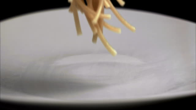 Slow motion close up linguine falling onto plate
