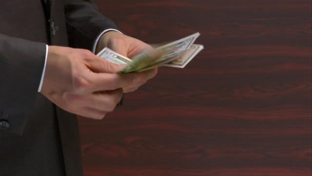 slow motion close up man counting stack of 50 dollar bills and tossing them - giving stock videos & royalty-free footage