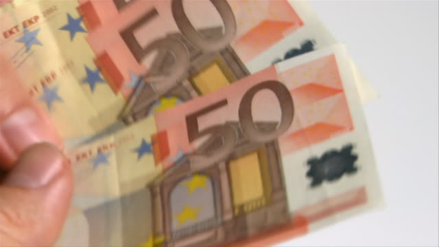 Slow motion close up man shuffling stack of 50 Euro notes