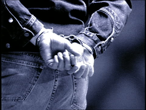 vídeos de stock, filmes e b-roll de b/w grainy slow motion close up man with hands handcuffed behind his back - algema