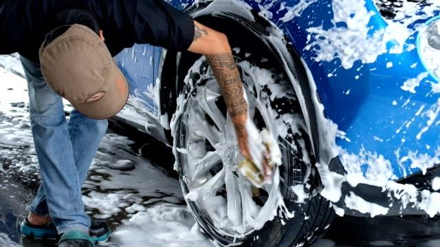 stockvideo's en b-roll-footage met langzame beweging, close-up van iemands hand reinigen van de auto met blauwe spons en hogedruk wassen - foam hand