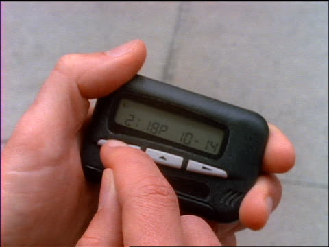 slow motion close up man's hands holding pager + checking pages on sidewalk - 1998 stock-videos und b-roll-filmmaterial