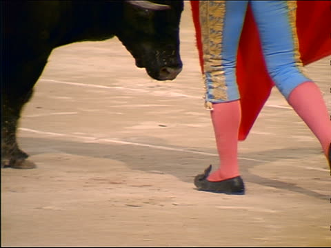 stockvideo's en b-roll-footage met slow motion close up matador's feet dancing as bull charges through cape + turns - herbivoor