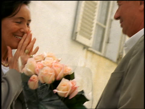 slow motion close up pan middle-aged man giving roses to surprised woman outdoors / they hug / corsica - mature couple stock videos & royalty-free footage
