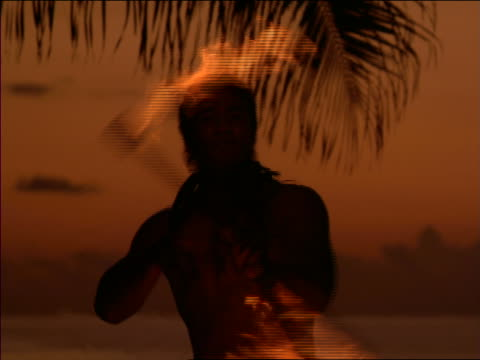 slow motion close up native man dancing with flaming torch at dusk / Hawaii