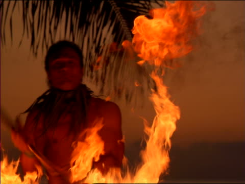 slow motion close up native man dancing with flaming torch at dusk / hawaii - 1997 stock videos & royalty-free footage