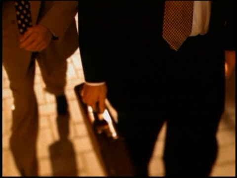 slow motion close up of 2 businessmen from chests down walking on street, carrying briefcases - krawatte stock-videos und b-roll-filmmaterial