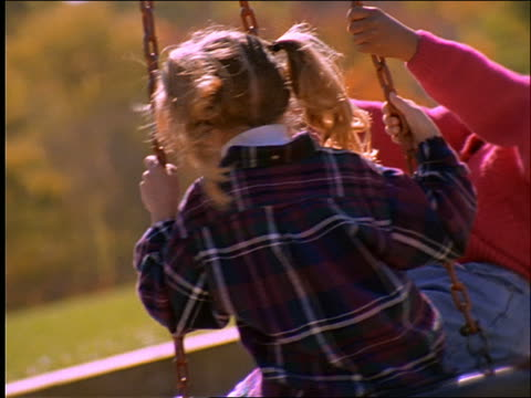 slow motion close up of 2 girls (1 black) spinning on tire swing / connecticut - tyre swing stock videos & royalty-free footage