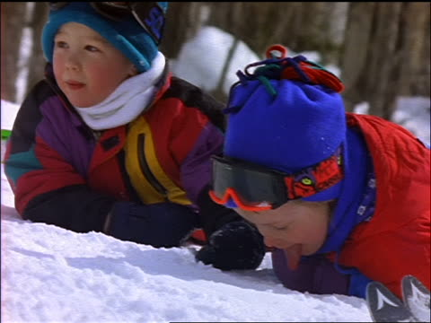 slow motion close up of 2 young children eating snow