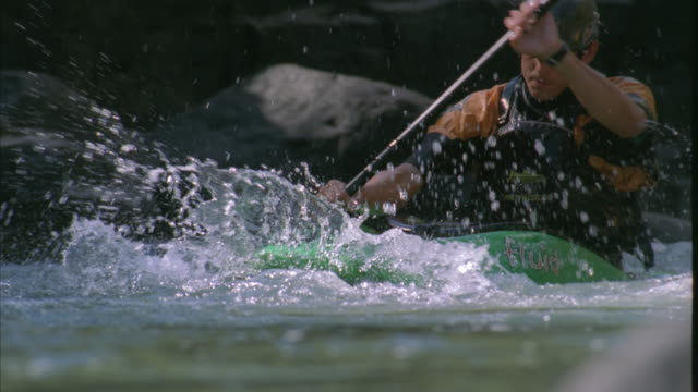 Slow motion close up of a kayaker paddling through the waters