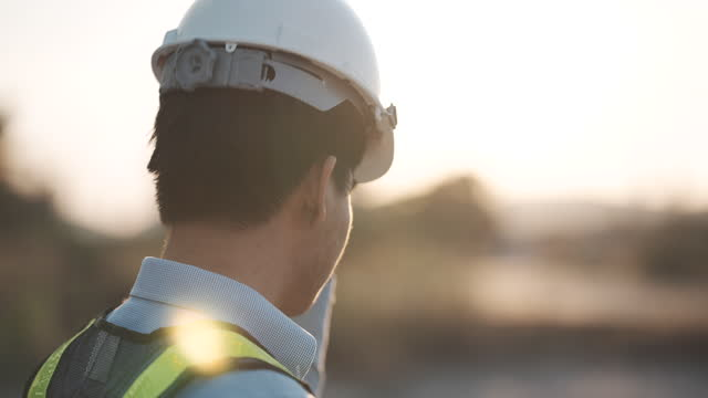 slow motion close up of a male engineer putting a construction helmet on at sunset, success, work and engineering concept. - safety stock videos & royalty-free footage