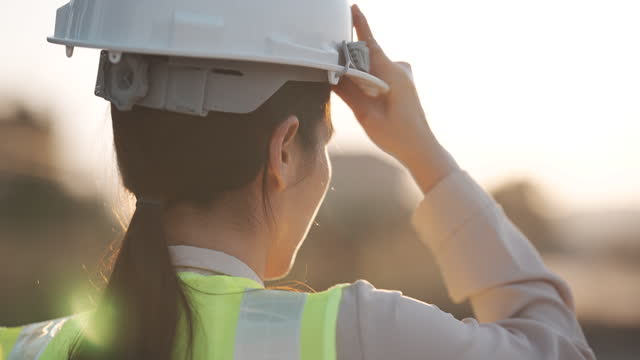 slow motion close up of a woman engineer putting a construction helmet on at sunset, success, work and engineering concept. - headwear stock videos & royalty-free footage