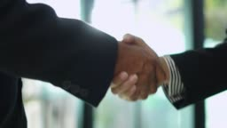 Slow motion: Close up of Asian business shaking hand.